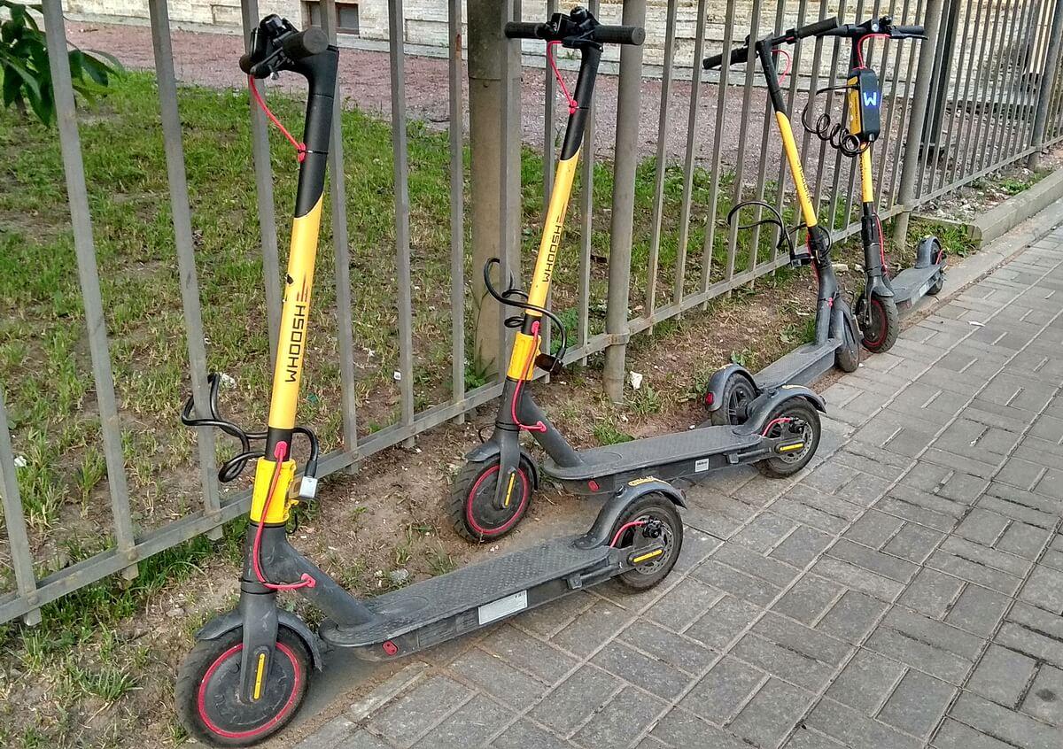 Электросамокаты Whoosh припаркованы у ограды